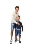 El adolescente feliz juega con su pequeño hermano alegre Foto de archivo