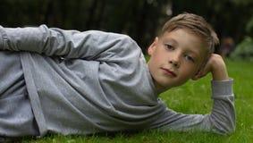 El adolescente feliz miente en un césped Imagenes de archivo