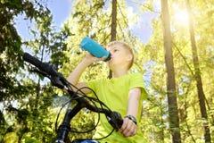 El adolescente feliz monta una bicicleta en madera de pino, en día soleado Fotografía de archivo libre de regalías