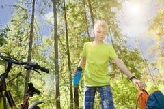 El adolescente feliz monta una bicicleta en madera de pino, en día soleado Imágenes de archivo libres de regalías