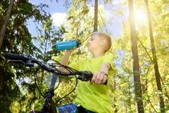 El adolescente feliz monta una bicicleta en madera de pino, en día soleado Imagen de archivo