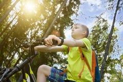 El adolescente feliz monta una bicicleta en madera de pino, en día soleado Foto de archivo
