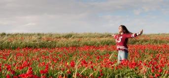 El adolescente feliz que se coloca en un campo rojo de la amapola florece Fotos de archivo