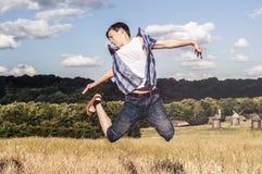 El adolescente feliz salta para arriba en el campo Foto de archivo