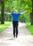 el adolescente feliz salta para arriba en un jardín del verano Fotografía de archivo libre de regalías