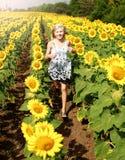 El adolescente feliz sonriente corre en el campo de girasoles Imagen de archivo libre de regalías