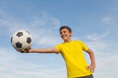 El adolescente feliz sostiene un balón de fútbol en sus manos, en un fondo Fotos de archivo libres de regalías