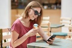 El adolescente femenino alegre que está alegre recibir el mensaje del novio, teléfono celular moderno de las aplicaciones, come e Imagenes de archivo