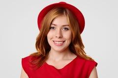 El adolescente femenino atractivo se prepara para tener partido con los amigos, vestidos en ropa y sombrero rojos elegantes, esta Imagen de archivo libre de regalías