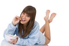 El adolescente femenino come el cereal sano para el desayuno Imágenes de archivo libres de regalías