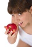 El adolescente femenino come la manzana roja Fotografía de archivo libre de regalías