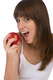 El adolescente femenino come la manzana roja para el desayuno Fotos de archivo