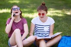 El adolescente femenino extático tiene charla divertida vía el teléfono celular, vestido en ropa del casula, pasa tiempo libre as Foto de archivo libre de regalías