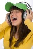 El adolescente femenino feliz disfruta de música con los auriculares Foto de archivo