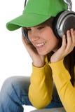 El adolescente femenino feliz disfruta de música con los auriculares Fotografía de archivo libre de regalías