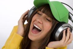 El adolescente femenino feliz disfruta de música con los auriculares Imagenes de archivo