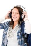 El adolescente femenino sonriente goza de los auriculares de la música Imágenes de archivo libres de regalías