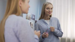 El adolescente femenino sonriente que pone en el labio glosa y que mira en el espejo, belleza almacen de video