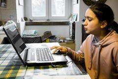 El adolescente femenino utiliza el ordenador en casa en la cocina en Imagenes de archivo