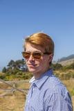 El adolescente fresco con las gafas de sol camina feliz en el prado Imagen de archivo libre de regalías