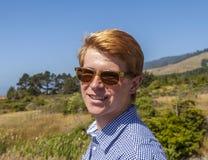 El adolescente fresco con las gafas de sol camina feliz en el prado Imagen de archivo