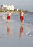 El adolescente goza el activar a lo largo de la playa Imagenes de archivo