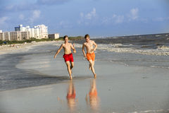 El adolescente goza el activar a lo largo de la playa Imagen de archivo libre de regalías