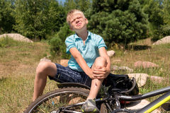 El adolescente ha caído de la bicicleta y fue traumatizado Foto de archivo