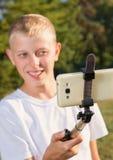 El adolescente hace el selfie en el parque Imagen de archivo