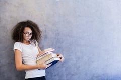 El adolescente hace una pausa la pared y sostiene los libros en sus manos Fotos de archivo libres de regalías