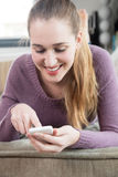 El adolescente hermoso alegre conectó con su teléfono móvil que buscaba Internet Imagenes de archivo