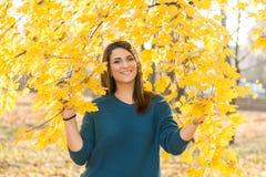 El adolescente hermoso con los apoyos que sonríe debajo del árbol en amarillo del otoño se va Foto de archivo libre de regalías