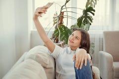 El adolescente hermoso con smartphone está haciendo un selfie Fotos de archivo libres de regalías