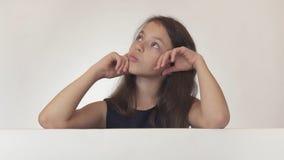 El adolescente hermoso de la muchacha reflexionaba sobre el cartel con la información en el fondo blanco Foto de archivo