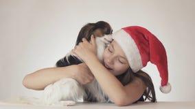 El adolescente hermoso en el sombrero de Santa Claus abraza feliz su perro en el fondo blanco Imagen de archivo libre de regalías