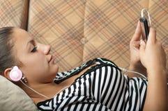 El adolescente hermoso escucha la música en el teléfono Fotos de archivo