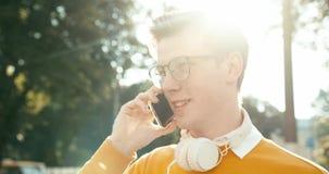 El adolescente hermoso joven con el pelo rubio en lentes está hablando feliz en el teléfono móvil en la calle cantidad 4k metrajes