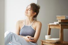 El adolescente hermoso joven que sostiene el teléfono elegante que sonríe con los ojos cerrados que se sientan en piso entre los  Imagen de archivo libre de regalías