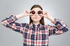 El adolescente hermoso la cubrió los ojos con los caramelos de chocolate redondos Foto de archivo