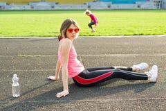 El adolescente hermoso que descansaba después de entrenamiento en el estadio, muchacha se sentó para relajarse, agua potable Imagenes de archivo