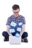 El adolescente hermoso que se sienta con el ordenador portátil y que envía mensajes es Foto de archivo