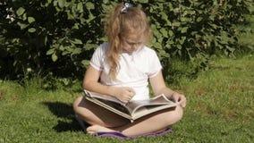 El adolescente hermoso que se sienta en una hierba en parque del verano y lee el libro Cámara lenta metrajes