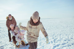 el Adolescente-hijo monta a su familia en un trineo en un invierno Imagen de archivo
