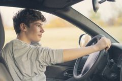 El adolescente joven aprende cómo conducir el coche f imagen de archivo
