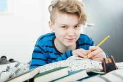 El adolescente joven contento que hace el suyo estudia Foto de archivo libre de regalías