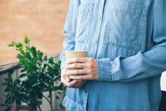 El adolescente joven en camisa casual azul de los vaqueros está bebiendo el café Imagen de archivo libre de regalías