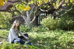 El adolescente joven hermoso que se sienta en un tronco de un árbol Imágenes de archivo libres de regalías