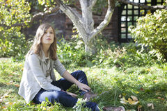 El adolescente joven hermoso que se sienta en un tronco de un árbol Imagen de archivo libre de regalías