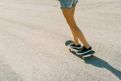 El adolescente joven patina en el monopatín, despegue, paso, salto Foto de archivo libre de regalías