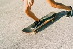 El adolescente joven patina en el monopatín, despegue, paso, salto Imágenes de archivo libres de regalías